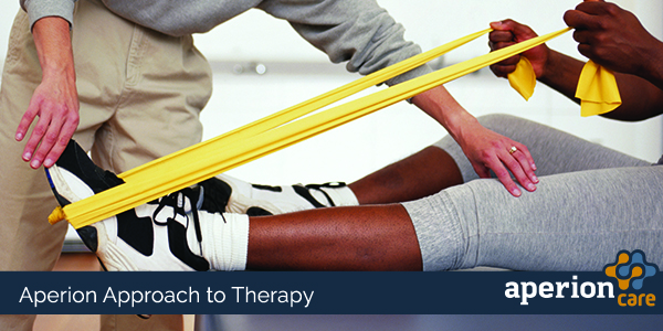 Therapist Uses Elastic Band to Work on Leg Exercises With Patient